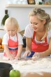La madre e la piccola figlia stanno cucinando nella cucina Spendendo tempo tutto insieme o concetto 'nucleo familiare' felice Fotografie Stock