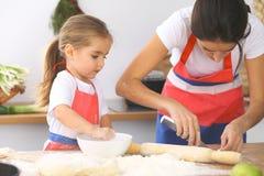 La madre e sua figlia sveglia prepara la pasta alla tavola di legno Pasticceria casalinga per pane o pizza Fondo del forno Fotografia Stock