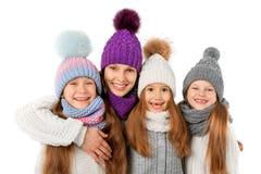 La madre ed i bambini svegli nell'inverno riscaldano i cappelli e le sciarpe su bianco Vestiti di inverno dei bambini Fotografia Stock