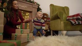 La madre ed il bambino allegri allegri svegli passano il loro tempo libero accanto all'albero di Natale a casa video d archivio