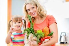 La madre ed il bambino che tengono un sacchetto della spesa hanno riempito dalle verdure Immagine Stock Libera da Diritti