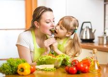 La madre ed il bambino mangiano le verdure in cucina immagini stock