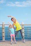 La madre ed il bambino nella forma fisica equipaggiano l'allungamento sull'argine Fotografia Stock