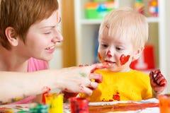La madre ed il bambino si divertono con le pitture Immagini Stock