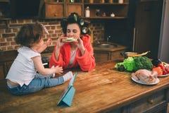 La madre ed il bambino si sono impegnati insieme in vestiti rivestenti di ferro di lavoro domestico Casalinga e bambino che fanno immagine stock