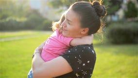 La madre ed il bambino stanno abbracciando e divertiresi all'aperto in natura, madre abbraccia la sua piccola figlia sveglia stock footage