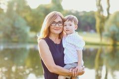 La madre ed il bambino stanno stando nel parco fotografia stock