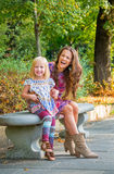 La madre ed il fare da baby-sitter sul banco in città parcheggiano Fotografie Stock