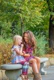 La madre ed il fare da baby-sitter sul banco in città parcheggiano Fotografia Stock