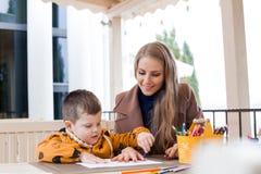 La madre ed il figlio estraggono le matite colorate mani del disegno fotografie stock
