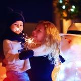 La madre ed il figlio felici celebrano il nuovo anno con le stelle filante ed il pupazzo di neve Fuoco sulle stelle filante Immagine Stock