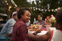La madre ed il figlio neri famiglia al 4 luglio arrostiscono col barbecue, si chiudono su Fotografie Stock