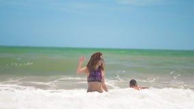 La madre ed il figlio saltano nel mare sulle onde, rejoise, si divertono stock footage