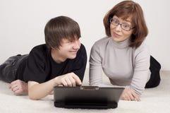 La madre ed il figlio sono insieme, lavoro con il calcolatore Immagine Stock