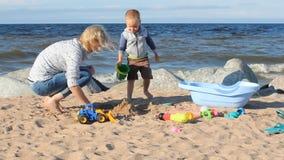 La madre ed il gioco da bambini con la sabbia sull'oceano puntellano stock footage