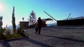 La madre ed il giovane figlio camminano attraverso il parco sulla via video d archivio