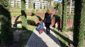 La madre ed il giovane figlio camminano attraverso il parco sulla via archivi video