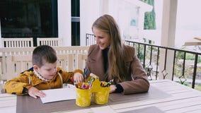 La madre ed il giovane figlio stanno disegnando ad una tavola video d archivio