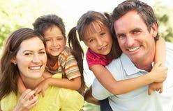 La madre ed il padre che danno i bambini trasportano sulle spalle fotografia stock