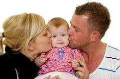 La madre ed il padre stanno baciando il bambino Immagine Stock