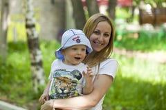 La madre ed il piccolo figlio giocano nel parco dell'estate Immagini Stock