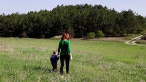 La madre ed il ragazzino vanno sul campo stock footage