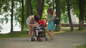La madre ed il suo amico danno il bambino in un'acqua del passeggiatore in una bottiglia video d archivio