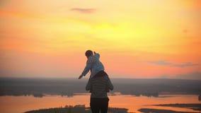La madre ed il suo piccolo figlio si divertono contro il color scarlatto del tramonto La madre tiene il bambino sulle spalle, le  stock footage