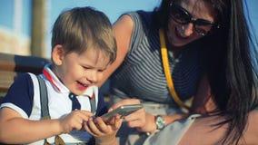 La madre ed il suo piccolo figlio sono ridenti e guardanti qualcosa sullo Smart Phone in parco stock footage