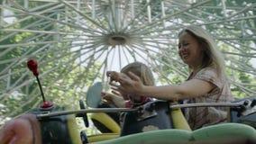 La madre ed il suo piccolo neonato stanno guidando sul trattore a cingoli nel parco di divertimenti 4k video d archivio