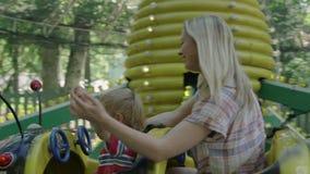 La madre ed il suo piccolo neonato stanno guidando sul trattore a cingoli nel parco di divertimenti 4k stock footage