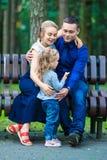 La madre, el padre feliz y la niña caminando en verano parquean Fotos de archivo libres de regalías