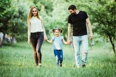 La madre, el padre feliz y la niña caminando en verano parquean Imágenes de archivo libres de regalías