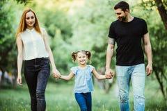 La madre, el padre feliz y la niña caminando en verano parquean Foto de archivo libre de regalías