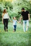 La madre, el padre feliz y la niña caminando en verano parquean Imagenes de archivo