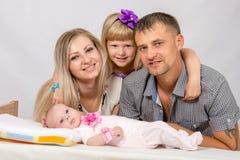 La madre, el padre, la hija y el bebé recién nacido de cinco años mira en la imagen Imagenes de archivo