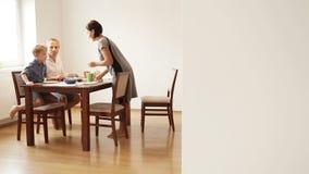 La madre, el padre y el pequeño hijo comienzan el desayuno de la mañana almacen de metraje de vídeo