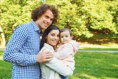 La madre, el padre y la hija están caminando en el parque imagenes de archivo