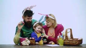 La madre, el padre y el hijo están pintando los huevos La familia feliz se está preparando para Pascua Conejito que lleva del muc almacen de video
