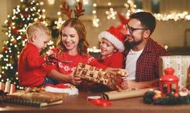 La madre, el padre y los niños de la familia de Y embalan los regalos de la Navidad fotografía de archivo libre de regalías