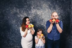 La madre embarazada, el padre barbudo, y poca hija están celebrando manzanas en sus manos y quieren comerlas foto de archivo libre de regalías