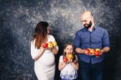 La madre embarazada, el padre barbudo, y poca hija están celebrando manzanas en sus manos y quieren comerlas imagen de archivo libre de regalías