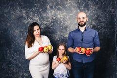 La madre embarazada, el padre barbudo, y poca hija están celebrando manzanas en sus manos y sonrisa fotos de archivo