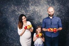 La madre embarazada, el padre barbudo, y poca hija están celebrando manzanas en sus manos y sonrisa imagenes de archivo