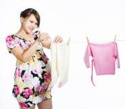La madre embarazada joven cuelga hacia fuera para secar un kidswear imágenes de archivo libres de regalías