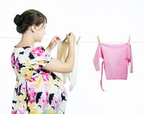 La madre embarazada joven cuelga hacia fuera para secar un kidswear fotografía de archivo