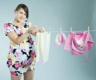 La madre embarazada joven cuelga hacia fuera para secar un kidswear foto de archivo libre de regalías