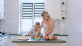 La madre enseña al hijo a tajar el queso Una madre hermosa joven con en la camisa blanca y el cocinero lindo del hijo en una coci almacen de video