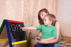 La madre enseña al niño imagen de archivo libre de regalías