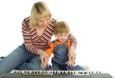 La madre enseña al piano del juego del bebé Imagen de archivo libre de regalías